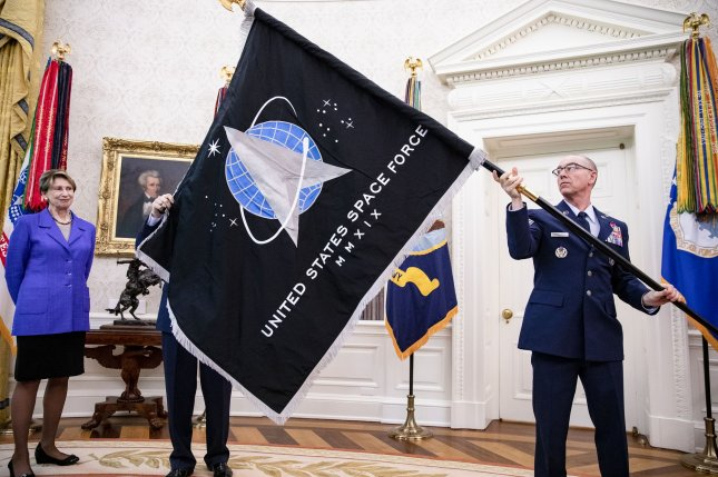 Gen. Jay Raymond (R), chief of Space Operations, CMSgt. Roger Towberman (C) and Secretary of the Air Force Barbara Barrett present President Donald Trump with the official flag of the U.S. Space Force in the Oval Office at the White House on Friday. Pool Photo by Samuel Corum/UPI