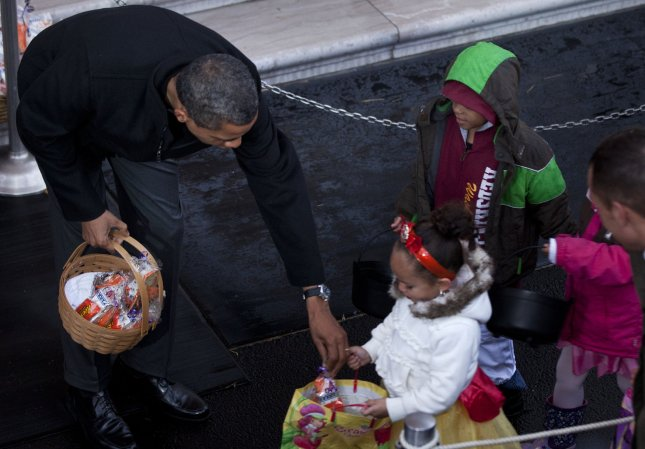 U.S. President Barack Obama hands out treats to a trick or treater at the White House October 29, 2011 in Washington, DC. President Barack Obama and First Lady Michelle Obama hosted military families and other trick or treaters for a Halloween party. UPI/Brendan Smialowski/POOL