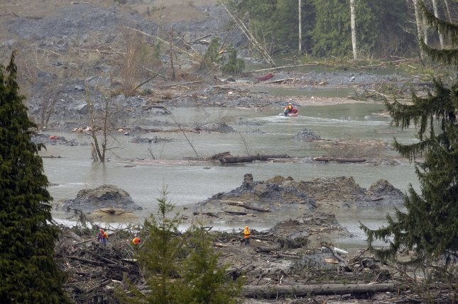 Search and rescue personnel work near the plateau above the soggy hillside on March 27, 2014 in Oso, Washington following a mudslide that buried the town, about 12 miles west of Darrington. (UPI/Ted Warren/Pool)
