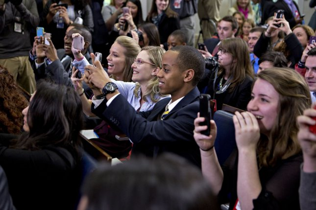 Journalism students react as U.S. President Barack Obama, not pictured, makes a surprise entrance during a college reporter day in the Brady Press Briefing Room of the White House in Washington, D.C., U.S., on Thursday, April 28, 2016. A media blitz by the White House and its allies has failed to crack Republican opposition to Obama's Supreme Court nominee, and it is all but certain the seat will remain vacant until after U.S. elections in November. Pool Photo by Andrew Harrer/UPI
