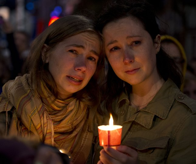 Two women attend a candlelight vigil for the Orlando shooting victims in the Castro District in San Francisco on Sunday. Forty-nine people died when a gunman opened fire in a gay nightclub in Orlando, Fla. Photo by Terry Schmitt/UPI