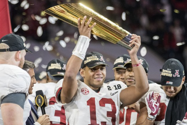 Alabama Crimson Tide quarterback Tua Tagovailoa (13) hoists the National Championship trophy after defeating the Georgia Bulldogs 26-23 in the College Football Playoff National Championship at Mercedes-Benz Stadium in Atlanta early Tuesday. Photo by Mark Wallheiser/UPI