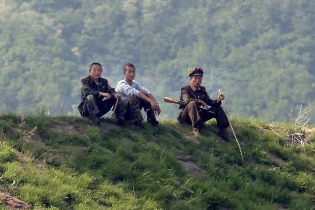 North Korean soldiers sit in the shade near the North Korean city Sinuiju, across the Yalu River from Dandong, China's largest border city with North Korea. Well-to-do families are required to send their teenage sons and daughters to serve in the military, but poor conditions are drawing complaints. File Photo by Stephen Shaver/UPI