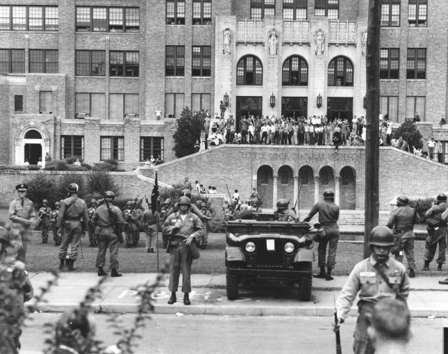 Original caption: White students look on as heavily guarded Negro students climb the steps of the Little Arkansas Central High School on September 26, 1957, on their way to classes. President Eisenhower was compelled to enforce the Supreme Court's public school desegregation decision with troops after the integrity of the court was challenged by Arkansas Governor Orval Faubus. UPI File Photo