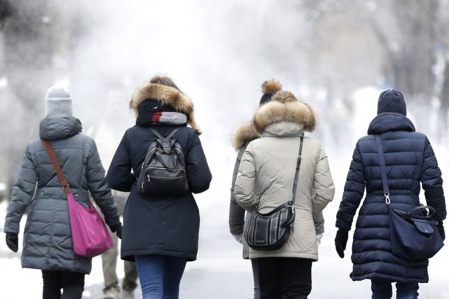 Pedestrians dressed for cold weather walk near Central Park in New York City on Monday. Photo by John Angelillo/UPI