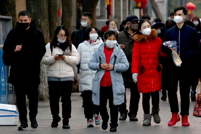 People wear protective respiratory masks in Beijing on Saturday. The U.S. State Department is arranging a chartered flight to evacuate U.S. diplomats and other Americans from Wuhan, China. Photo by Stephen Shaver/UPI