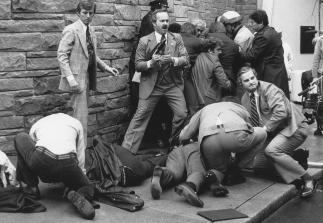 Agents tend to Presidential Press Secretary James Brady and a wounded police office after subduing John Hinckley Jr. (right background), who got off six rounds at President Ronald Reagan on March 30, 1981. Photo by Don Rypka/UPI