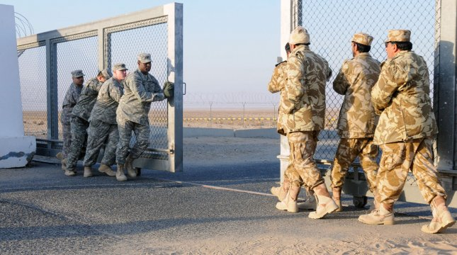 This December 18, 2011 DOD image shows U.S. and Kuwaiti service members closing a gate between Kuwait and Iraq following the final convoy of Operation New Dawn passing through. The last convoy that crossed the border signaled the end of the transition of troops and equipment from Iraq as Operation New Dawn came to a close. UPI/Jordan Johnson/DOD