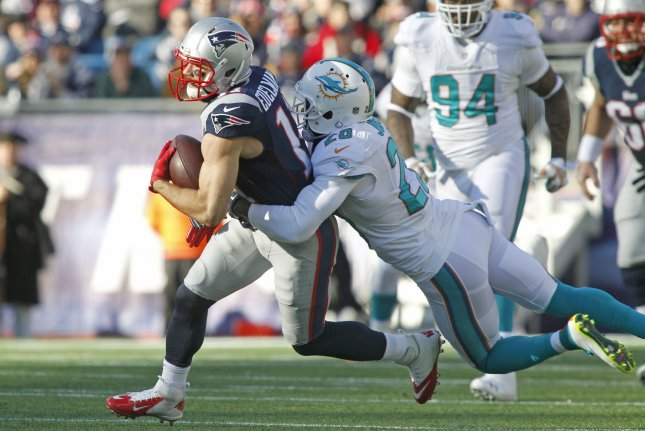 New England Patriots wide receiver Julian Edelman (11) is dragged down by Miami Dolphins safety Reshad Jones (20) on a 15-yard reception in the first quarter on December 14, 2014 at Gillette Stadium in Foxborough, Massachusetts. File photo by Matthew Healey/UPI
