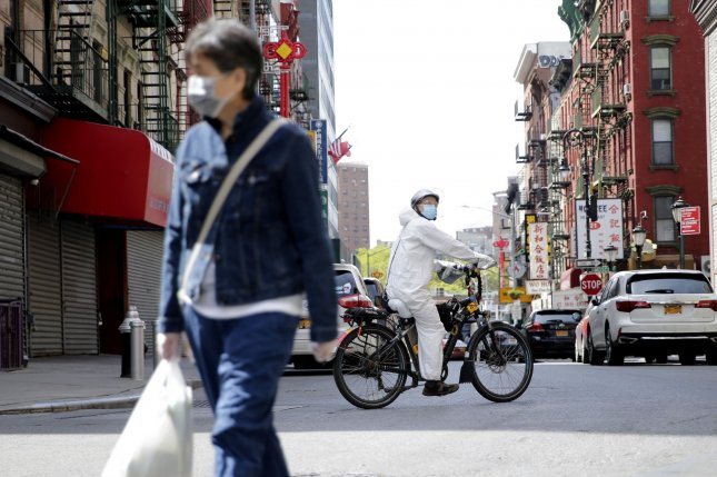 A man wears a protective suit and face mask while riding a bicycle on Mott street in the Chinatown section of Manhattan in New York City in May. Photo by John Angelillo/UPI