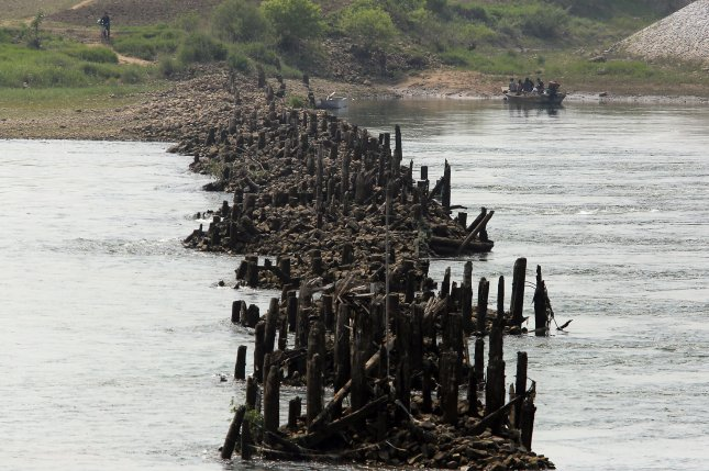 North Koreans get in a boat next to a destroyed bridge connecting China and North Korea, in Dandong, China's largest border city with North Korea on May 30. North Korea was hit by heavy flooding in three provinces between Aug. 1 and 5, according to the U.N. File Photo by Stephen Shaver/UPI