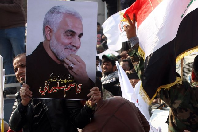 Members of an Iran-backed Iraqi militia carry pictures of slain military commander Qassem Soleimani as they stand next to his coffin during a funeral procession in Baghdad on January 4. File photo by Ibrahim Jassam /UPI