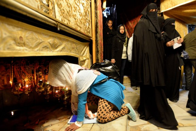 A Christian pilgrim kneels to pray in the grotto in the Church of Nativity, traditionally believed to be the site where Jesus Christ was born, in the biblical town of Bethlehem, West Bank, December 23, 2013. Christians of the world are expected to flock to Bethlehem to celebrate Christmas on December 25. UPI/Debbie Hill