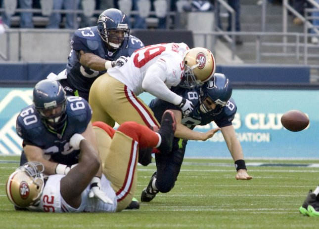 Seattle Seahawks' quarterback Matt Hasselbeck looses the ball after getting hit by San Francisco 49ers' linebacker Manny Lawson (99) in the first quarter at Qwest Field in Seattle on December 6, 2009. The Seahawks beat the 49er's 20-17. (UPI /Jim Bryant)