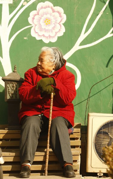 The process of aging is different for men and women An elderly Chinese woman sits in the midday sun in downtown Beijing. UPI/Stephen Shaver