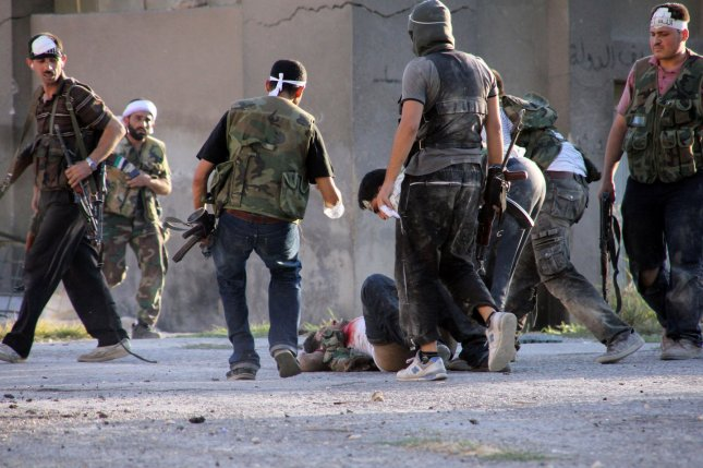 Free Syrian Army fighters help a wounded comrade during street fighting against soldiers of President Bashar al-Assad in Aleppo, Syria on September 8, 2012. UPI/Ahmad Deeb