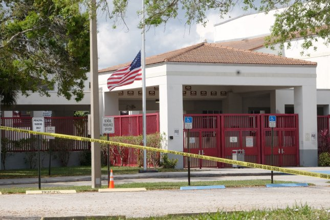A flag flies at half-staff and crime scene tape surrounds Marjory Stoneman Douglas High School in Parkland, Fla., on February 18 -- four days after a gunman killed 17 people and wounded more than a dozen others in a shooting attack. File Photo by Gary Rothstein/UPI
