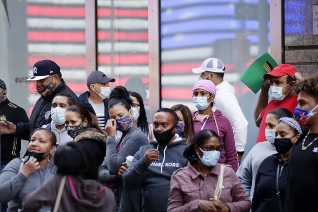 Pedestrians are seen wearing face masks Tuesday in New York City's Times Square. More than 900 people died of COVID-19 on Tuesday, according to researchers. Photo by John Angelillo/UPI