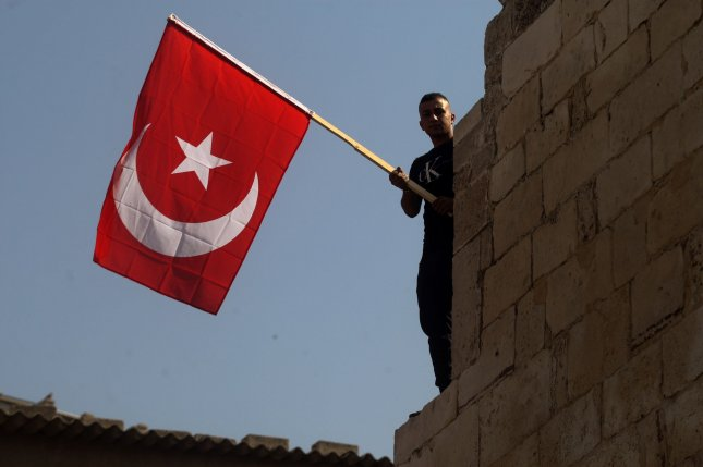 A demonstrator holds a Turkish flag at an October 14 rally to support Turkey's military action in northeastern Syria, in Khan Younis in the southern Gaza Strip. Photo by Ismael Mohamad/UPI
