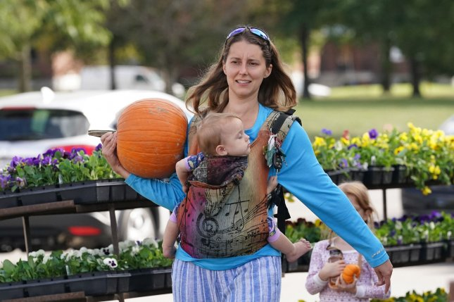 A woman balances a Halloween pumpkin and a baby in St. Louis, Mo., in October. File Photo by Bill Greenblatt/UPI