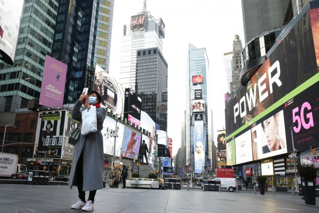 A woman wearing a face mask stops to take a photo surrounded by zero nearby pedestrian traffic in Times Square in New York City on Wednesday. Photo by John Angelillo/UPI
