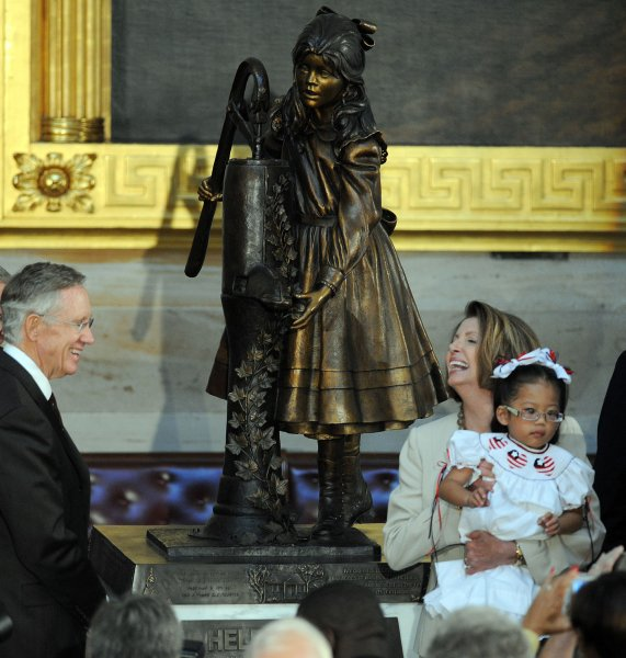 Senate Majority Leader Harry Reid, D-NV, and Speaker of the House Nancy Pelosi, D-CA, who is holding four-year-old Malia Thibado, share a laugh as a statue of Helen Keller is unveiled in the Capitol Rotunda on Capitol Hill in Washington on October 7, 2009. Thaibado is a student from the Alabama Institute for Deaf and Blind. UPI/Roger L. Wollenberg