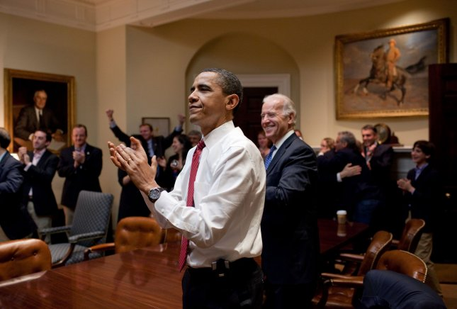 U.S. President Barack Obama, Vice President Joe Biden, and senior staff applaud in the Roosevelt Room of the White House, as the House passes the health care reform bill, late on March 21, 2010. At left is a painting of President Franklin D. Roosevelt and at right is President Teddy Roosevelt. UPI/Pete Souza/White House