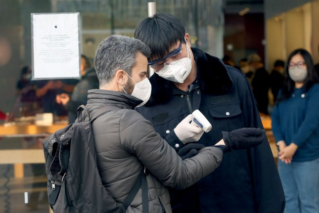 An Apple security guard checks the temperature of people visiting the Apple store due to the threat of the the deadly coronavirus spreading in Beijing on Monday, February 24. Photo by Stephen Shaver/UPI