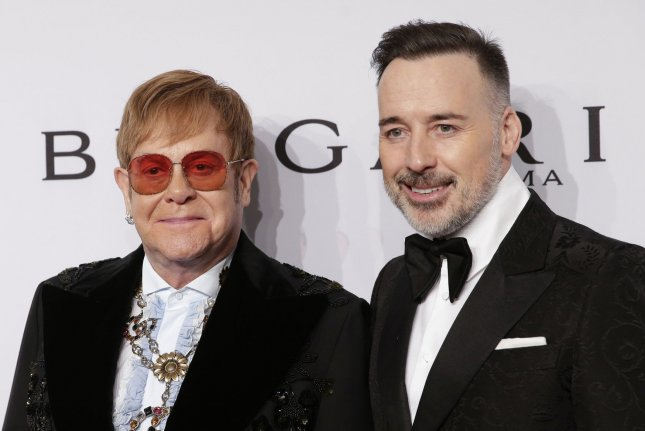Elton John (L), pictured with David Furnish, took the stage with Taron Egerton at the Elton John AIDS Foundation Academy Awards viewing party Sunday. File Photo by John Angelillo/UPI
