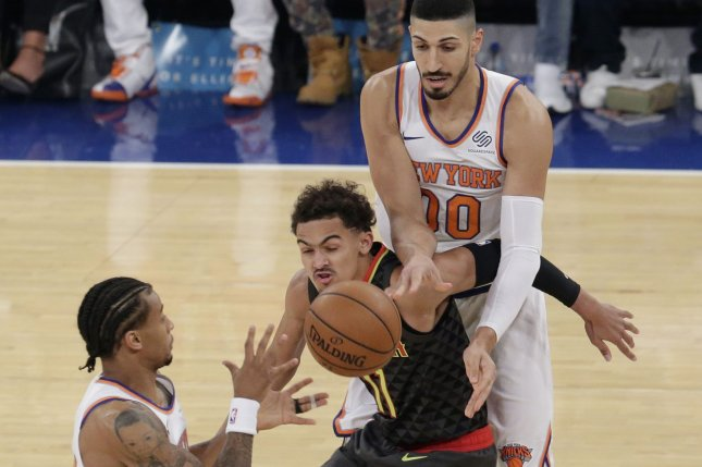 New York Knicks' Enes Kanter passes the ball to Trey Burke past Atlanta Hawks rookie Trae Young in the first half on October 17 at Madison Square Garden in New York City. Photo by John Angelillo/UPI