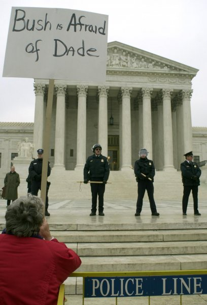 A Gore supporter holds a sign as police guard the outside of the United States Supreme Court in Washington, D.C. on December 11, 2000. George W. Bush and Al Gore attorneys made their oral arguments on the Florida vote recount before the United States Supreme Court Bush and Gore supporters rallied outside. Photo by Bill Clark/UPI