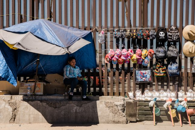 A street peddler sells souvenirs next to the border fence that divides the U.S. and Mexico in Mexicali, Mexico on April 4.President Donald Trump seeks to stop immigration by imposing tariffs on Mexican goods. File Photo by Ariana Drehsler/UPI