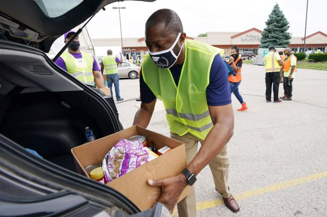 St. Louis Public School Superintendent Dr. Calvin Adams loads food and school supplies into a vehicle on Saturday during a supply give-a-way to aid residents amid the coronavirus pandemic in St. Louis, Mo. Photo by Bill Greenblatt/UPI