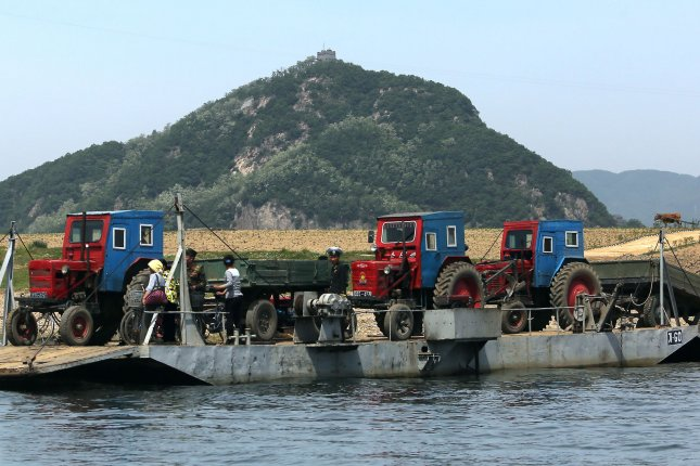 North Koreans wait to cross part of the Yalu River at a makeshift pontoon dock near Sinuiju, across the Yalu River from Dandong, China's largest border city with North Korea. Pyongyang's state enterprises are competing for trade permits and industrial activity has subsequently increased, a North Korea source said. File Photo by Stephen Shaver/UPI