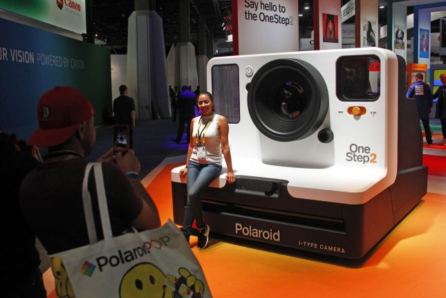 An attendee poses in front of a giant model of a Polaroid instant camera during the 2018 International CES at the Las Vegas Convention Center on January 9. On November26, 1948, the first commercial Polaroid camera was sold. The inventor of the device and founder of Polaroid Corp., Edwin H. Land, obtained some 533 patents before his death in 1991. File Photo by James Atoa/UPI