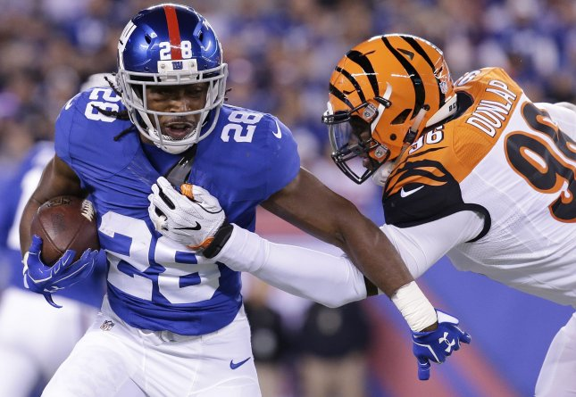 New York Giants running back Paul Perkins tries to elude Cincinnati Bengals lineman Carlos Dunlap during a game in 2016. Photo by John Angelillo/UPI