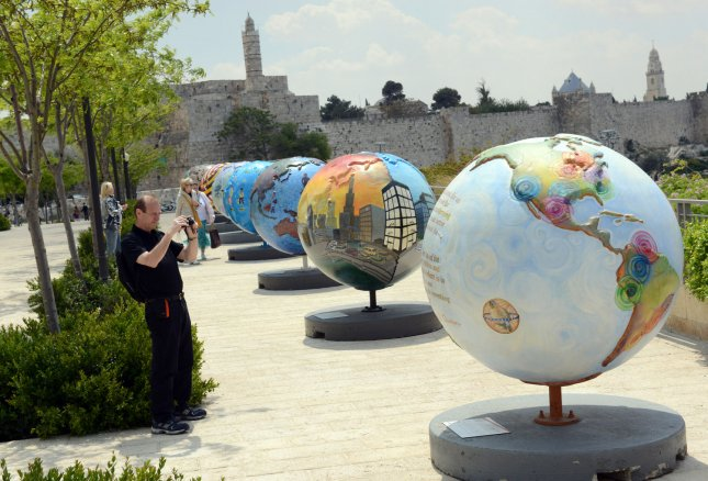 A tourist takes a photo of a globe, part of the Cool Globes Project, an international public art exhibition featuring 18 oversized globes designed to inspire a call to environmental action, near Jaffa Gate, outside the Old City of Jerusalem, Israel, April 19, 2013. The globes, an initiative of the Chicago based non-profit Cool Globes, aims to raise awareness of climate change. The globes were brought to Jerusalem within the framework of the First International Jerusalem Symposium on Green and Accessible Pilgrimage which takes place in Jerusalem this week. UPI/Debbie Hill