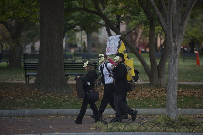 Protesters walk through Lafayette Park following Anonymous' Million Mask March in 2013, outside of the White House in Washington, D.C. This week, a hacker posted the names of several politicians he said were linked to the Ku Klux Klan, coinciding with similar posts from Anonymous. File Photo by Kevin Dietsch/UPI