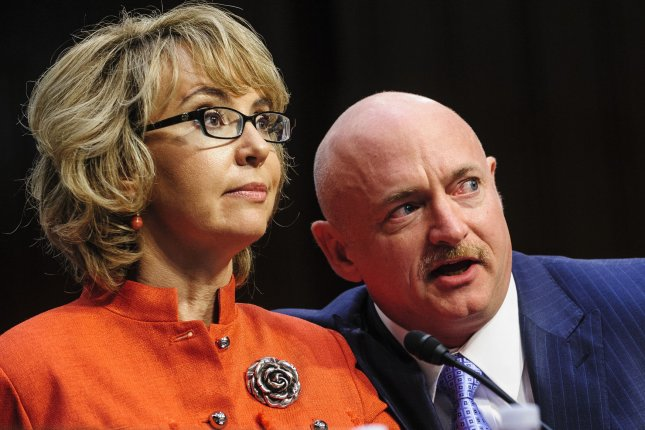 Retired Navy Capt. Mark Kelly sits with his wife Rep. Gabrielle Giffords as she makes a statement before a Senate Judiciary Committee hearing on gun violence on Capitol Hill in Washington, DC on January 30, 2013. UPI/Pete Marovich