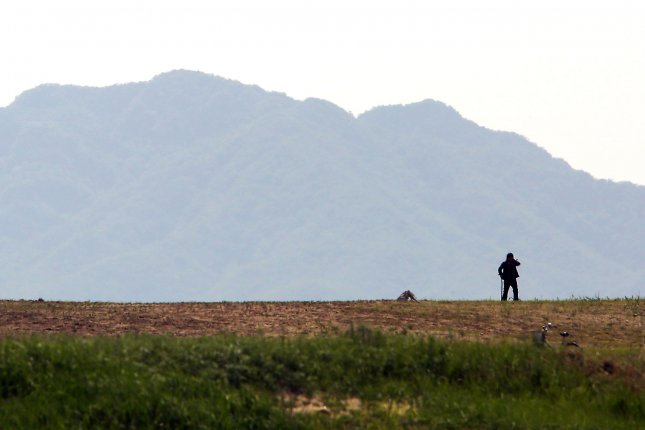 A North Korean sheep herder watches his flock near the North Korean city of Sinuiju, across the Yalu River from Dandong, China's largest border city with North Korea. Many North Korean defectors flee the country by crossing into China. Photo by Stephen Shaver/UPI
