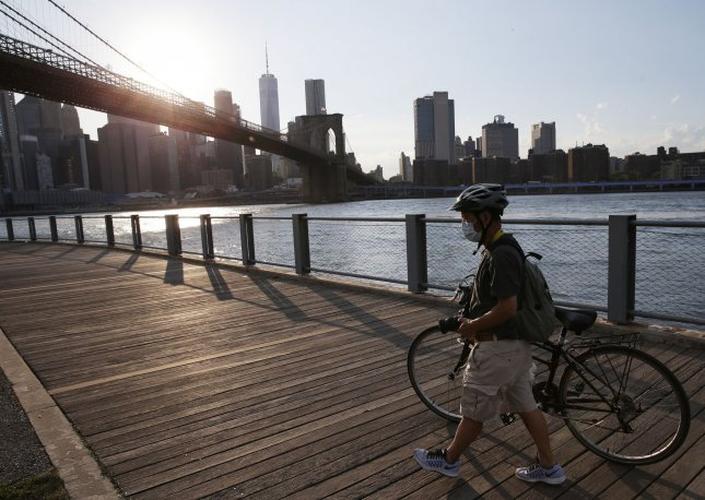 A man wearing a protective face mask walks his bicycle in Brooklyn Bridge Park on Thursday. New York City entered phase 2 of a four-part reopening plan Monday after being closed for 3 months due to COVID-19. Photo by John Angelillo/UPI