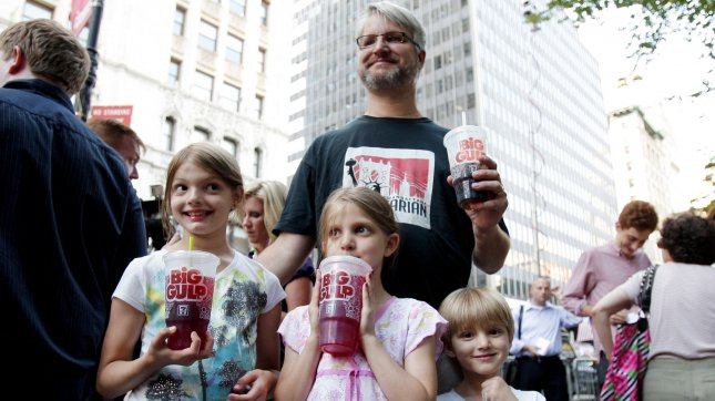 Jim Sara, Alana and Benjamin Lesczynski hold large drinks at the Million Big Gulp March protest to express opposition to Mayor Michael R. Bloomberg's proposal to prohibit licensed food service establishments from using containers larger than 16 ounces to serve high-calorie drinks at City Hall Park in New York City on July 9, 2012. UPI/John Angelillo