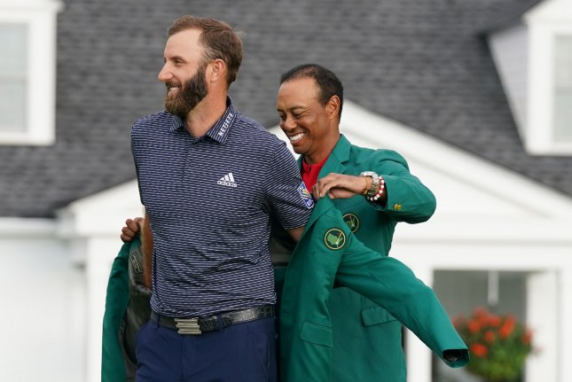 2019 Masters winner Tiger Woods puts the Green Jacket on 2020 champion Dustin Johnson after the final round of the 2020 Masters on Sunday at Augusta National Golf Club in Augusta, Ga. Photo by Kevin Dietsch/UPI