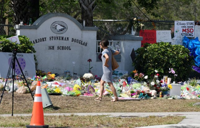 A parent looks at the makeshift memorial while waiting for her child to be dismissed from class at Marjory Stoneman Douglas High School on February 28 in Parkland, Fla. Dozens of teachers and hundreds of students at the protested the reassignment of four administrators on Tuesday. File Photo by Gary Rothstein/UPI