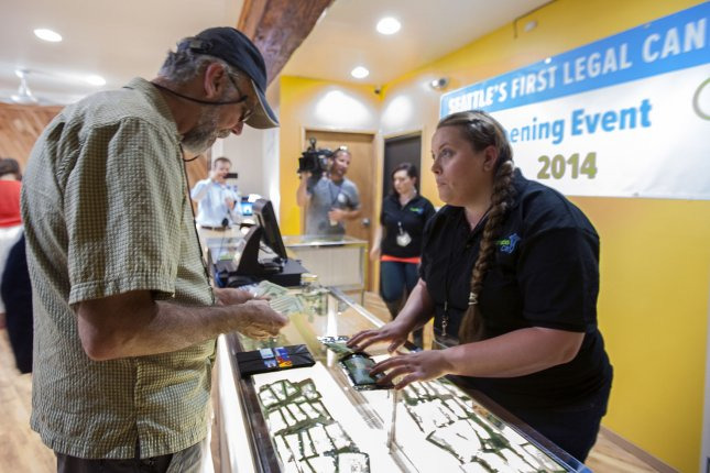 Mark Lucas (L) counts money to purchase marijuana as Cannabis City employee Pam Fenstermacher talks to him about his purchase at the first legal recreational marijuana store on July, 8, 2014 in Seattle. On Friday, Gov. Jay Inslee said he will offer pardons with misdemeanor marijuana convictions before recreation pot became legal. File photo by Jim Bryant/UPI