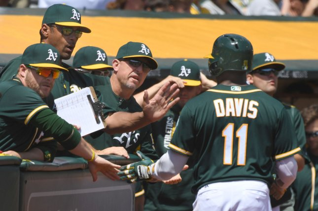 Oakland Athletics' Rajai Davis (11) is congratulated after scoring following a leadoff double off Texas Rangers pitcher Martin Perez in the first inning at the Oakland Coliseum in Oakland, Califoria on April 19, 2017. File photo by Terry Schmitt/UPI