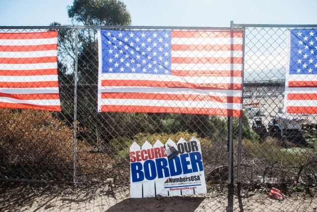 American flags hang on a fence in San Ysidro, Calif., December 15 during an America First rally at the port of entry along the United States-Mexico border. Photo by Ariana Drehsler/UPI