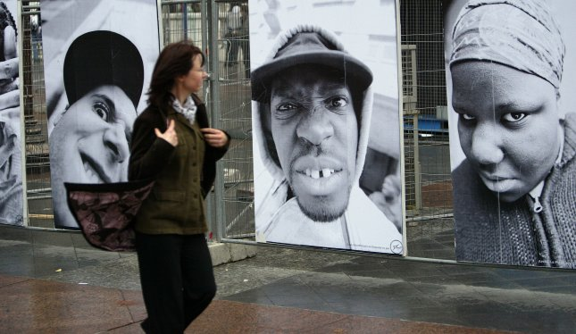 Pedestrians walk past self-portraits of teenagers from the Paris suburbs during an exhibition at Paris City Hall on November 16, 2006. The exhibit marks the one year anniversary of the three-week riots that swept through largely immigrant housing projects across France, following the accidental death of two teenagers who were being chased by policemen in Clichy-sous-Bois, near Paris. (UPI Photo/Eco Clement)