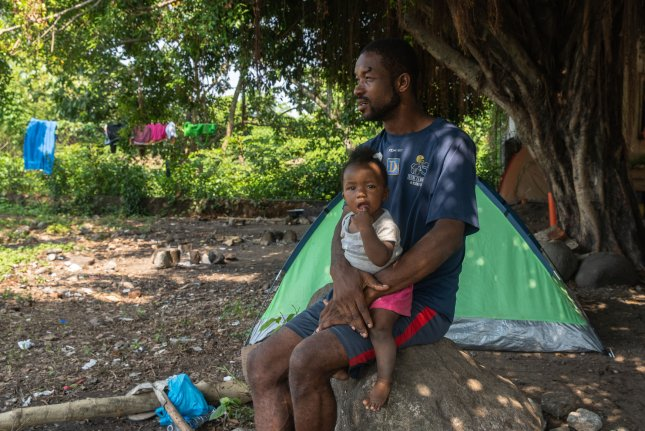 Cineac Kinchel from Haiti sits with daughter Michele in Tapachula, Mexico, on Thursday in a shantytown built in April by Africans and Haitian migrants waiting for appointments with immigration officials. Photo by Ariana Drehsler/UPI