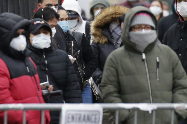 People wearing protective face masks wait on line to be tested for Coronavirus at Elmhurst Hospital Center on Tuesday. Photo by John Angelillo/UPI